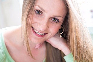 Blonde woman with braces smiling