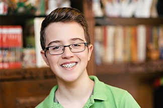 Teenage boy with glasses and braces smiling